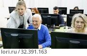 Купить «Portrait of modern elderly people working on computers with young female teacher while attending pc class», видеоролик № 32391163, снято 26 февраля 2019 г. (c) Яков Филимонов / Фотобанк Лори