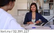 Купить «Positive businesswoman talking to female colleague in office», видеоролик № 32391227, снято 13 июня 2019 г. (c) Яков Филимонов / Фотобанк Лори
