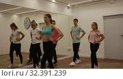 Купить «Cheerful teenage boys and girls dancing synchronous group choreography in dance hall», видеоролик № 32391239, снято 21 сентября 2019 г. (c) Яков Филимонов / Фотобанк Лори