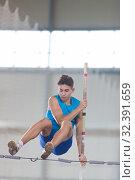 Купить «Pole vaulting indoors - young man jumping over the partition leaning on the pole», фото № 32391659, снято 1 ноября 2019 г. (c) Константин Шишкин / Фотобанк Лори