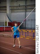 Купить «Pole vaulting indoors - young man standing on the runway holding a pole», фото № 32391667, снято 1 ноября 2019 г. (c) Константин Шишкин / Фотобанк Лори