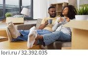 Купить «happy couple drinking coffee moving to new home», видеоролик № 32392035, снято 3 ноября 2019 г. (c) Syda Productions / Фотобанк Лори