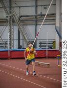 Купить «Pole vaulting indoors - a man in yellow shirt standing on the track with a pole», фото № 32396235, снято 1 ноября 2019 г. (c) Константин Шишкин / Фотобанк Лори