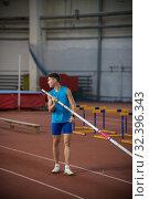 Купить «Pole vaulting - a young guy is standing with a pole in hand», фото № 32396343, снято 1 ноября 2019 г. (c) Константин Шишкин / Фотобанк Лори