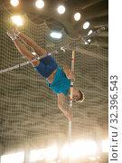 Купить «Pole vaulting - guy is jumping over the bar holding on to a pole», фото № 32396543, снято 1 ноября 2019 г. (c) Константин Шишкин / Фотобанк Лори