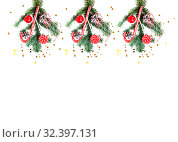 Christmas decorations and tree branch on white background. Composition collage with striped candy, red apple, cone, striped thread and confetti. Flat lay. New Year and Christmas mood. Стоковое фото, фотограф Papoyan Irina / Фотобанк Лори