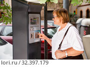 Купить «Smiling middle aged woman using parking machine to pay for car parking on summer city street», фото № 32397179, снято 16 февраля 2020 г. (c) Яков Филимонов / Фотобанк Лори