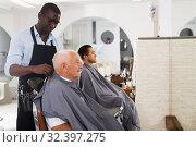 Купить «African barber putting on hairdresser cape to elderly client», фото № 32397275, снято 22 августа 2019 г. (c) Яков Филимонов / Фотобанк Лори