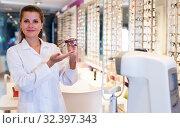 Купить «Female optician is offering glasses in medical shop», фото № 32397343, снято 27 августа 2019 г. (c) Яков Филимонов / Фотобанк Лори