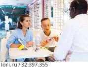 Купить «Female and male opticians consulting young male customer», фото № 32397355, снято 27 августа 2019 г. (c) Яков Филимонов / Фотобанк Лори