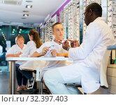 Купить «Ophthalmologist helping boy to choose glasses», фото № 32397403, снято 27 августа 2019 г. (c) Яков Филимонов / Фотобанк Лори