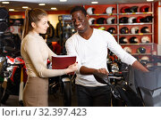 Купить «Polite smiling female seller communicating with male customer in modern motorcycle salon», фото № 32397423, снято 16 января 2019 г. (c) Яков Филимонов / Фотобанк Лори