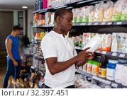 Focused muscular African man choosing sports nutrition products in shop, reading content label. Стоковое фото, фотограф Яков Филимонов / Фотобанк Лори