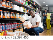 Купить «Focused muscular African man choosing sports nutrition products in shop, reading content label», фото № 32397455, снято 8 декабря 2019 г. (c) Яков Филимонов / Фотобанк Лори