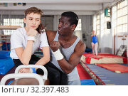 Купить «Male coach talking with upset teenage boy on gymnastic equipment at acrobatic center», фото № 32397483, снято 17 января 2019 г. (c) Яков Филимонов / Фотобанк Лори