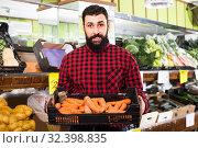 Купить «seller showing carrots», фото № 32398835, снято 15 ноября 2016 г. (c) Яков Филимонов / Фотобанк Лори