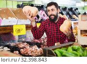 Купить «Young male seller offering pumpkins», фото № 32398843, снято 15 ноября 2016 г. (c) Яков Филимонов / Фотобанк Лори