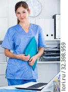 Купить «Young doctor in blue overall holding clipboard», фото № 32398959, снято 31 июля 2017 г. (c) Яков Филимонов / Фотобанк Лори