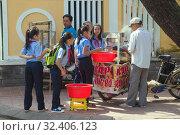 Купить «Вьетнамские школьницы покупают попкорн у уличного торговца. Хюэ, Вьетнам», фото № 32406123, снято 8 января 2016 г. (c) Виктор Карасев / Фотобанк Лори