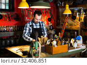 Купить «Worker processing leather for belt», фото № 32406851, снято 13 ноября 2019 г. (c) Яков Филимонов / Фотобанк Лори