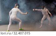 Купить «Two young women fencers having a dynamic training duel in the studio», видеоролик № 32407015, снято 10 апреля 2020 г. (c) Константин Шишкин / Фотобанк Лори