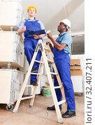 Купить «Men contractors working indoors», фото № 32407211, снято 4 мая 2018 г. (c) Яков Филимонов / Фотобанк Лори