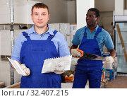 Купить «Surprised builder with plastering tools», фото № 32407215, снято 4 мая 2018 г. (c) Яков Филимонов / Фотобанк Лори