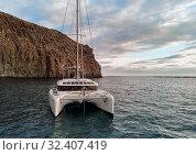 Купить «Rear view moored lonely modern catamaran in calm waters of Atlantic Ocean near rocky mountain. Tenerife, Canary Islands, Spain. Concept of lifestyle, adventure activity, beautiful nature and freedom», фото № 32407419, снято 15 октября 2019 г. (c) Alexander Tihonovs / Фотобанк Лори