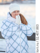 Купить «Frozen and smiling woman covering her ears with hands in woolen mittens, standing outdoor at cold weather in cold winter season», фото № 32407883, снято 19 января 2014 г. (c) Кекяляйнен Андрей / Фотобанк Лори