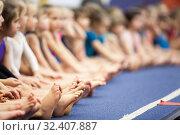 Купить «Children barefoot legs, beginner gymnasts of three and four old ages sitting in line in a sport school», фото № 32407887, снято 25 декабря 2013 г. (c) Кекяляйнен Андрей / Фотобанк Лори