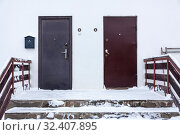Two steel doors are on one common doorstep with one and two numerals, porch covered with snow. Стоковое фото, фотограф Кекяляйнен Андрей / Фотобанк Лори
