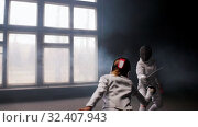 Купить «Two young women having a fencing duel in the smoky studio», видеоролик № 32407943, снято 30 марта 2020 г. (c) Константин Шишкин / Фотобанк Лори