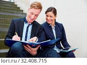 Zwei lächelnde Geschäftsleute arbeiten unterwegs mit Akte und Tablet PC. Стоковое фото, фотограф Zoonar.com/Robert Kneschke / age Fotostock / Фотобанк Лори