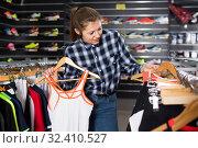 Купить «smiling tennis woman is looking on modern shirt for sport in the store», фото № 32410527, снято 7 февраля 2018 г. (c) Яков Филимонов / Фотобанк Лори