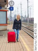 Eine junge Frau mit Koffer wartet auf dem Bahnsteig eines Bahnhofes auf ihren Zug. Zugverspätungen. Стоковое фото, фотограф Zoonar.com/Erwin Wodicka - wodicka@aon.at / age Fotostock / Фотобанк Лори