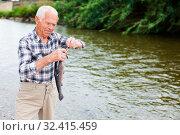 Купить «Adult fisherman removing catch from hook», фото № 32415459, снято 10 июня 2018 г. (c) Яков Филимонов / Фотобанк Лори
