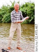 Купить «Mature fisherman examining catch», фото № 32415467, снято 10 июня 2018 г. (c) Яков Филимонов / Фотобанк Лори