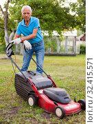 Купить «Positive elderly man with lawnmower when mowing the lawn», фото № 32415571, снято 30 мая 2020 г. (c) Яков Филимонов / Фотобанк Лори