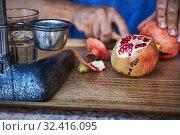 Купить «Street vendor peels ripe pomegranate for squeezing juice», фото № 32416095, снято 26 сентября 2019 г. (c) Олег Белов / Фотобанк Лори