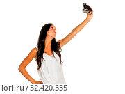 Eine junge Frau hat Spaß während sie sich selber mit einem alten Fotoapparat fotografiert. Selfie. Стоковое фото, фотограф Zoonar.com/Erwin Wodicka / age Fotostock / Фотобанк Лори