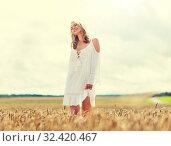 Купить «smiling young woman in white dress on cereal field», фото № 32420467, снято 31 июля 2016 г. (c) Syda Productions / Фотобанк Лори
