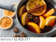Купить «pot with hot mulled wine, orange slices and spices», фото № 32420511, снято 4 октября 2018 г. (c) Syda Productions / Фотобанк Лори