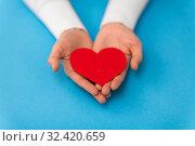 Купить «hands holding red heart shape on blue background», фото № 32420659, снято 12 декабря 2018 г. (c) Syda Productions / Фотобанк Лори