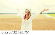 Купить «happy young woman in flower wreath on cereal field», фото № 32420751, снято 31 июля 2016 г. (c) Syda Productions / Фотобанк Лори