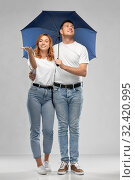 Купить «happy couple in white t-shirts with umbrella», фото № 32420995, снято 6 октября 2019 г. (c) Syda Productions / Фотобанк Лори