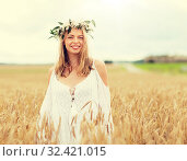 Купить «happy young woman in flower wreath on cereal field», фото № 32421015, снято 31 июля 2016 г. (c) Syda Productions / Фотобанк Лори
