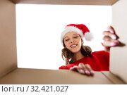 Купить «happy young woman looking into open christmas gift», фото № 32421027, снято 9 декабря 2018 г. (c) Syda Productions / Фотобанк Лори