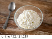 Купить «close up of cottage cheese in bowl on wooden table», фото № 32421219, снято 16 августа 2018 г. (c) Syda Productions / Фотобанк Лори