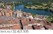 Купить «Aerial view of Cazeres cityscape on banks of Garonne river overlooking Catholic church of Our Lady of Cazeres, France», видеоролик № 32421935, снято 19 июля 2019 г. (c) Яков Филимонов / Фотобанк Лори