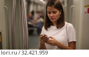 Young woman browsing and typing messages on phone in subway car. Стоковое видео, видеограф Яков Филимонов / Фотобанк Лори